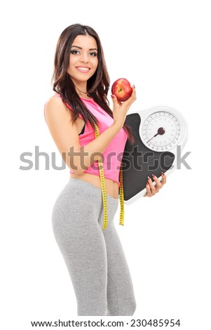 Woman holding a weight scale and an apple isolated on white background - stock photo