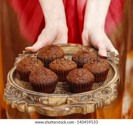 Woman holding a wooden tray with chocolate muffins