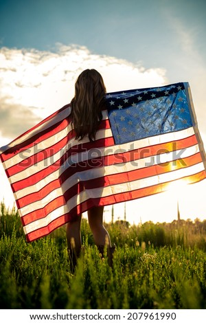 Woman holding American Flag in sunlight - stock photo