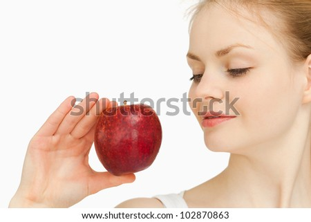 Woman holding an apple while looking at it against white background