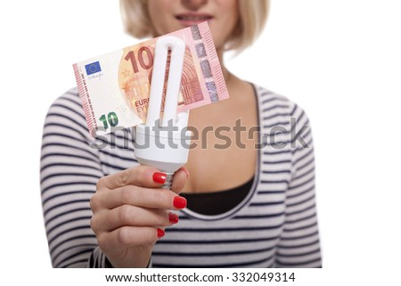 Woman holding an eco-friendly light bulb with a 10 Euro banknote threaded through it in a conceptual image of efficiency and savings