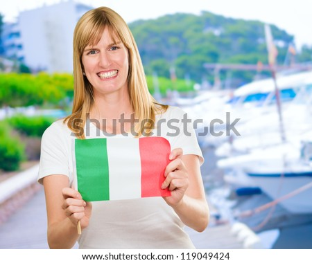woman holding an italian flag at a port - stock photo