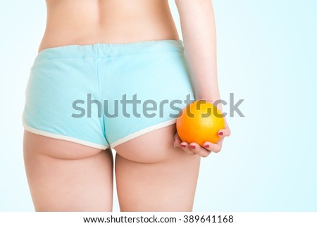 Woman Holding an Orange Against Her Thighs, isolated in blue - stock photo