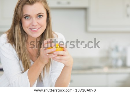 Woman holding an orange juice in kitchen