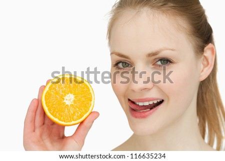 Woman holding an orange while placing her tongue on her lips against white background - stock photo