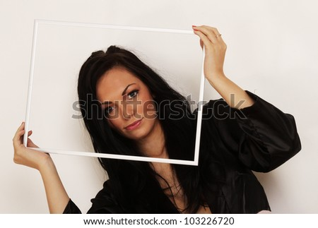 Woman holding and looking through a picture frame with sultry expression - stock photo