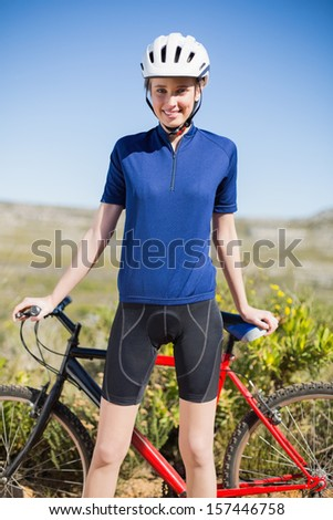 Woman holding and standing in front of bike looking at camera in the countryside - stock photo