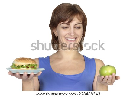 woman holding apple and burger