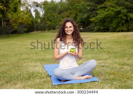 woman holding apple and sitting on the yoga-mat. Outdoor - stock photo