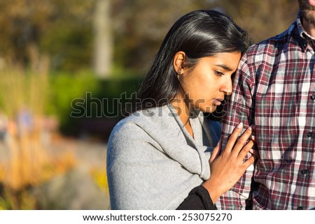 Woman holding arm of her rejecting partner - stock photo