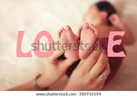 Woman holding baby feet closeup. Love concept. Childhood. Motherhood. - stock photo