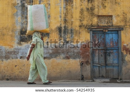Woman holding bag on her head. Picture in taken in India.