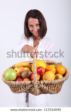 Woman holding basket of fruit