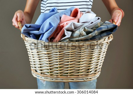 Woman holding basket with clothes on gray background - stock photo