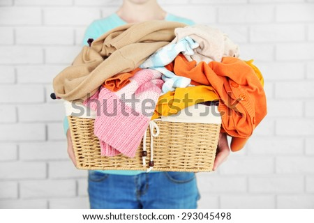 Woman holding basket with heap of different clothes, on bricks wall background - stock photo