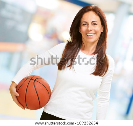Woman holding basketball, indoor - stock photo