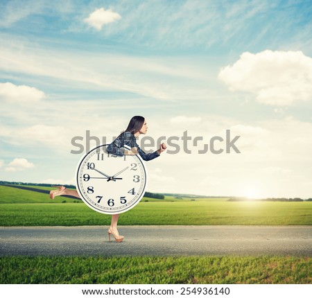woman holding big clock and running forward on the road at outdoor - stock photo