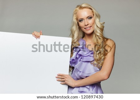 Woman holding blank board over gray background - stock photo