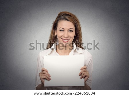Woman holding blank card banner white paper isolated on grey wall office  background Portrait happy young smiling female. Positive face expressions, emotions. Advertisement concept  - stock photo