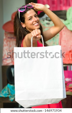 Woman holding blank shopping bags after buying clothes in sales. Successful and happy shopper. - stock photo
