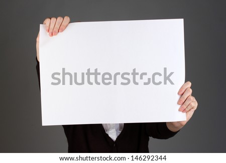 Woman holding blank sign in front her face, on color background - stock photo
