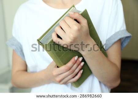 Woman holding book close up - stock photo