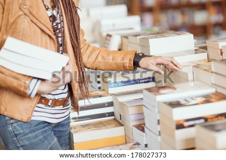 Woman holding books at a bookshop.
