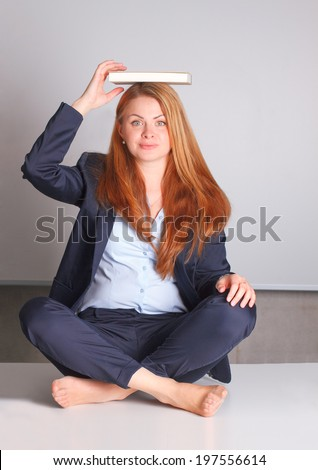 Woman holding books on her head - stock photo