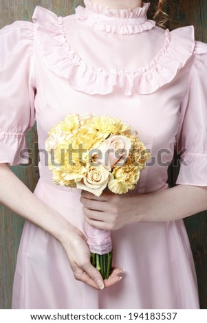 Woman holding bouquet of yellow carnation and pink roses