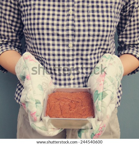 Woman holding brownie taken out of oven, retro filter effect - stock photo