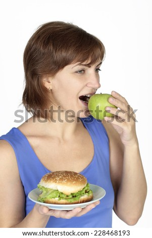 woman holding burger and eating apple
