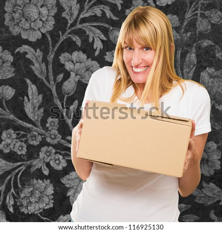 Woman Holding Cardboard box against a floral pattern background - stock photo