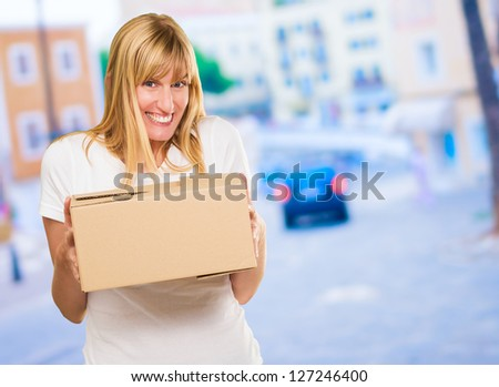 Woman Holding Cardboard box against a street background - stock photo
