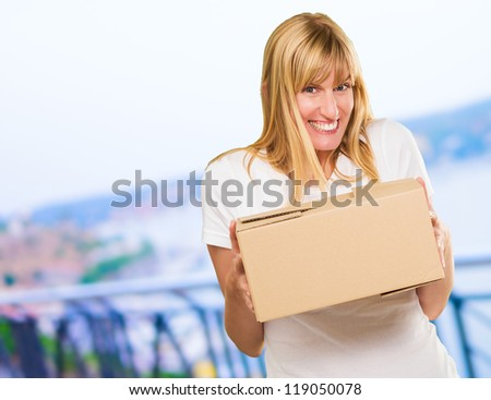Woman Holding Cardboard box, outdoor - stock photo