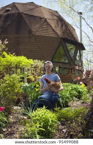 Woman holding chicken in her garden - stock photo