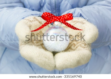 Woman holding christmas ball in her arms outdoor in winter - stock photo