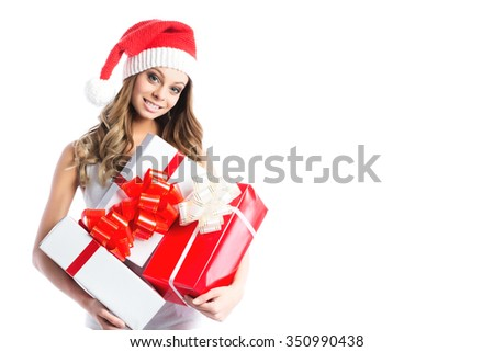 Woman holding Christmas gifts. Beautiful young female model isolated on white background. - stock photo