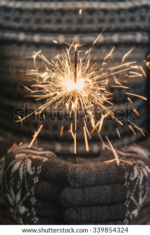 Woman holding Christmas Sparkler against gray background - stock photo
