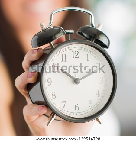 Woman Holding Clock, Indoors
