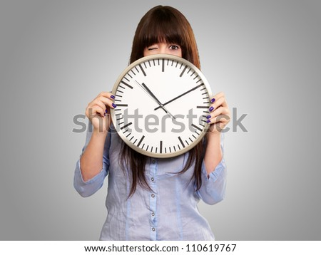 Woman Holding Clock Winking Isolated On Grey Background