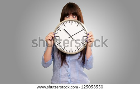Woman Holding Clock With Squinted Eyes Isolated On gray Background