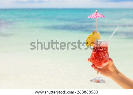 Woman holding cocktail on tropical beach - stock photo