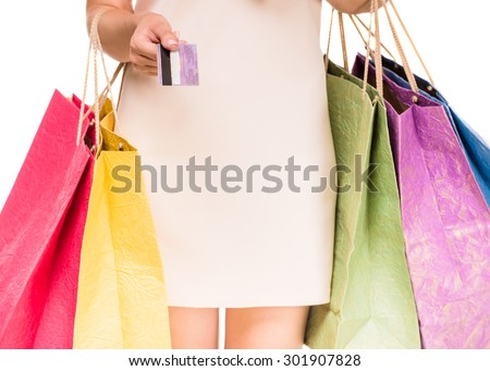 Woman holding colored shopping bags and credit card on white background. Close-up. - stock photo