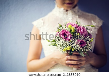 Woman holding colorful bouquet with her hands in wedding day - stock photo