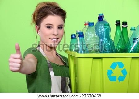 Woman holding crate of plastic bottles - stock photo