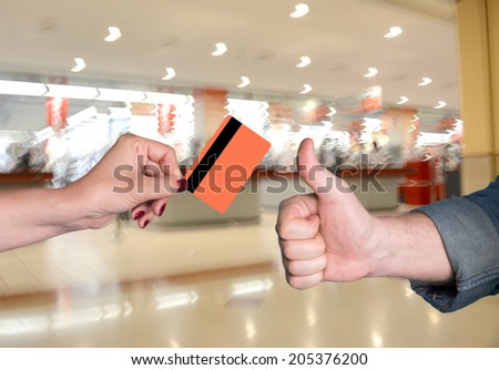 Woman holding credit card, man gesturing thumb up at shopping mall - stock photo