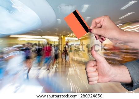 Woman holding credit card, man gesturing thumb up at shopping mall - stock photo