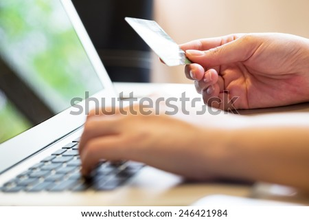 woman holding credit card on laptop for online shopping concept - stock photo