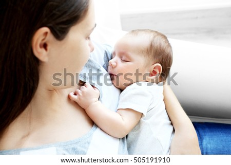 Woman holding cute sleeping baby, close up view