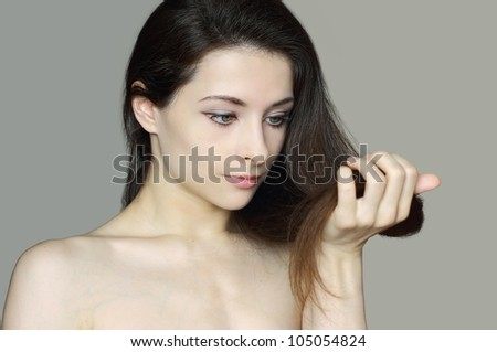 Woman holding damaged hair and unhappy looking. Closeup isolated portrait of beautiful upset lady. Hair care concept - stock photo